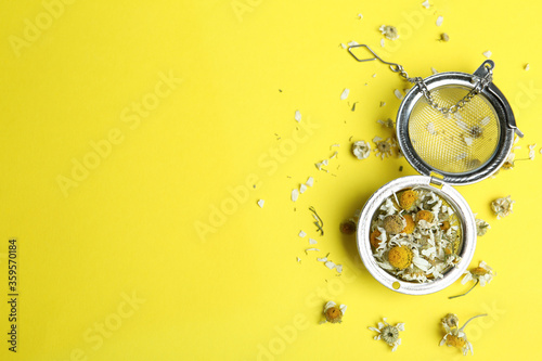 Fototapeta Dry chamomile flowers in infuser on yellow background, flat lay
