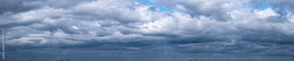 Fototapeta Panorama of dramatic rainy cloudy blue sky. Cumulus clouds are white and gray outdoors.