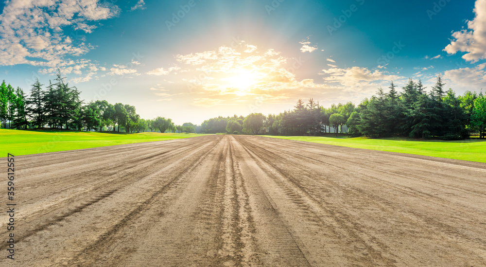 Fototapeta Rural dirt road ground and green forest at sunrise.