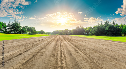 Fototapeta Rural dirt road ground and green forest at sunrise. obraz