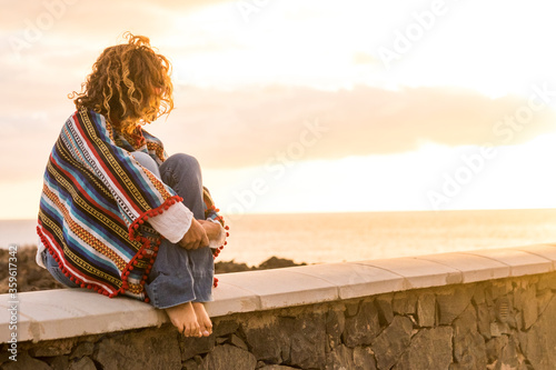 Photo Unrecognizable lonely woman sit down on a wall looking and enjoying the sunset o