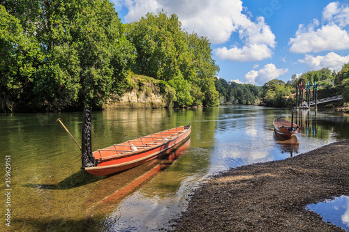 Photo Two Maori waka (traditional canoes) with carved prows on the Waikato River, New
