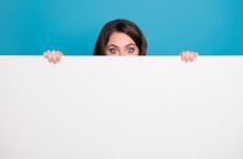 Photo Of Pretty Funny Crazy Lady Hold Hands Empty Advertisement Banner Peeking Eyes Hiding Face Tricky Read Novelty Surprise Isolated Blue Color Background