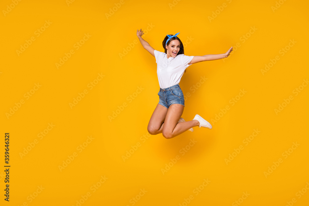 Fototapeta Full size photo of dreamy lovely cute excited girl jump raise hands enjoy spring free time weekend holiday wear good look blue headband sneakers isolated over bright color background
