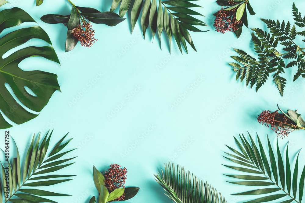 Fototapeta Summer composition. Tropical flowers and leaves on blue background. Summer concept. Flat lay, top view, copy space