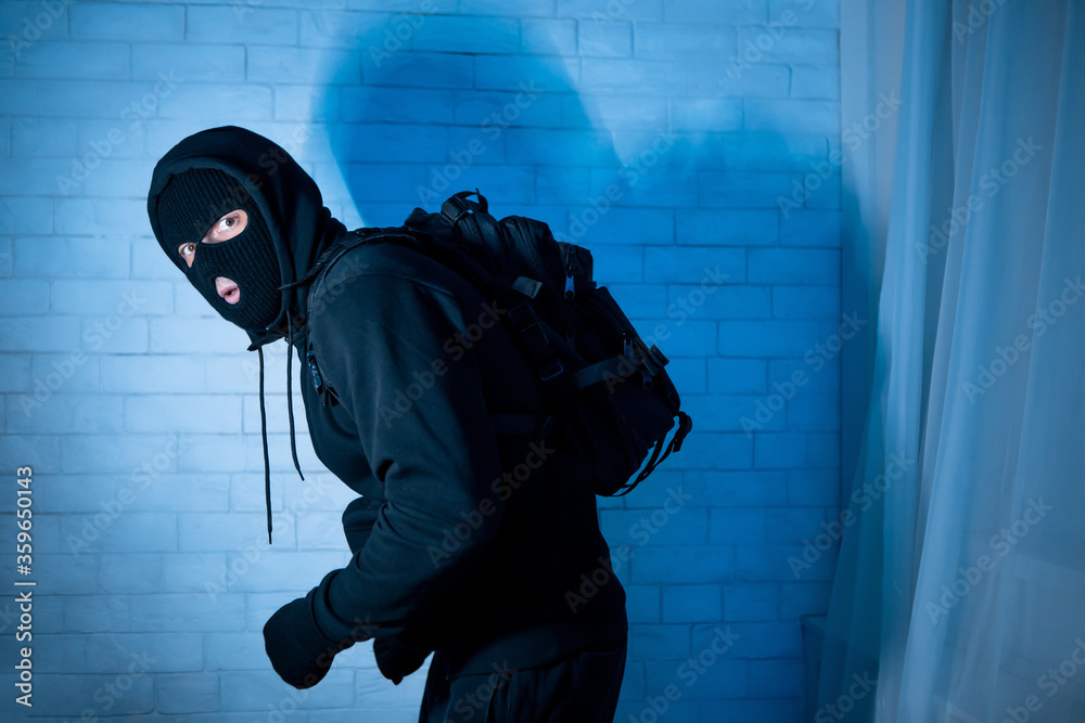 Fototapeta Sneaky scared robber ready to steal something at home