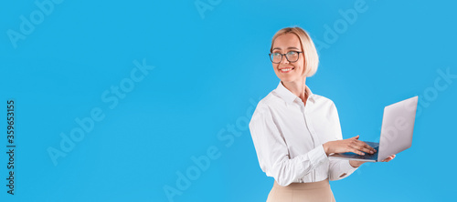 Obraz Happy millennial business lady with modern laptop on blue background, space for text - fototapety do salonu