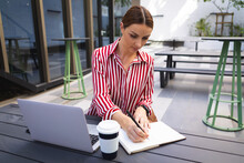 Caucasian Woman Working On A Computer And Taking Notes In A Sunny Day