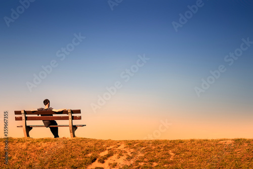Fotografering young man resting alone on a bench in an empty landscape at dusk
