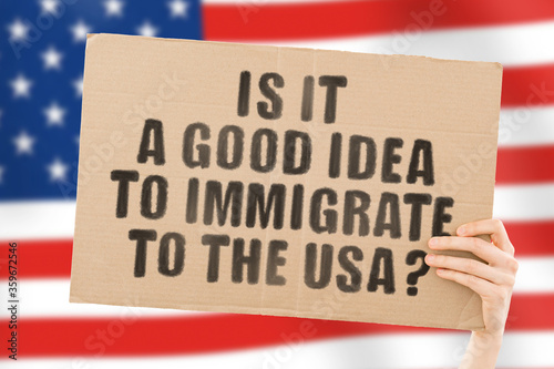Valokuva The phrase  Is it a good idea to immigrate to the USA?  on a banner in men's hand with blurred American flag on the background