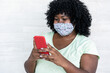 canvas print picture - Happy black girl using smartphone outdoor - Young curvy african female having fun watching videos on mobile phone while wearing face protective mask - Coronavirus lifestyle concept - Focus on hands