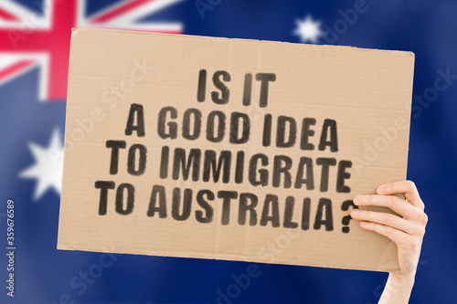 Valokuvatapetti The question  Is it a good idea to immigrate to Australia?  on a banner in men's hand with blurred Australian flag on the background