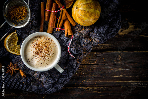 Fototapeta Autumn sweet hot drink, Chai Buttered Rum, Pumpkin Pie or Pumpkin Spice Coffee Latte. Cozy autumn background with traditional latte cup, spices and old sweater, on rustic wooden background obraz