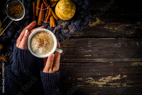 Fototapeta Autumn sweet hot drink, Chai Buttered Rum, Pumpkin Pie or Pumpkin Spice Coffee Latte. Cozy autumn background. Girl hold traditional latte cup in hands, on rustic wooden background obraz
