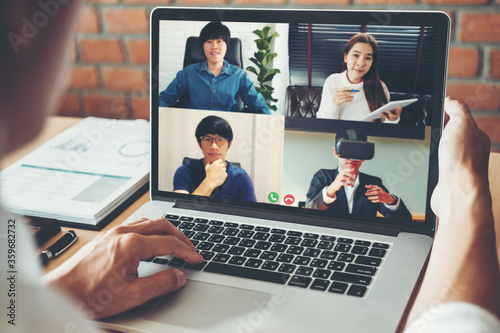 Fototapeta Asian man working from home use Smart working and video conference online meeting with Asian team using laptop and tablet online in video call for new projects obraz na płótnie