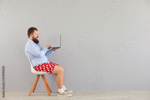 Papel de parede Funny fat man in a blue shirt and red shorts sitting on a chair working online using a laptop on a gray background