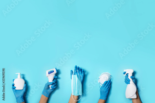 Fototapeta Raised hands in medical gloves holding masks, sanitizers, soap, non contact thermometer on blue background. Banner. Copy space. Health protection equipment during quarantine Coronavirus pandemic obraz