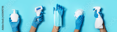 Fotomural Raised hands in medical gloves holding masks, sanitizers, soap, non contact thermometer on blue background