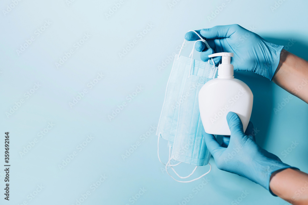 Fototapeta Hands in gloves holding soap bottle and medical face mask on blue background. Copy space. Preventive measures to protect against coronavirus. Products to stay safe during pandemic covid19 quarantine.