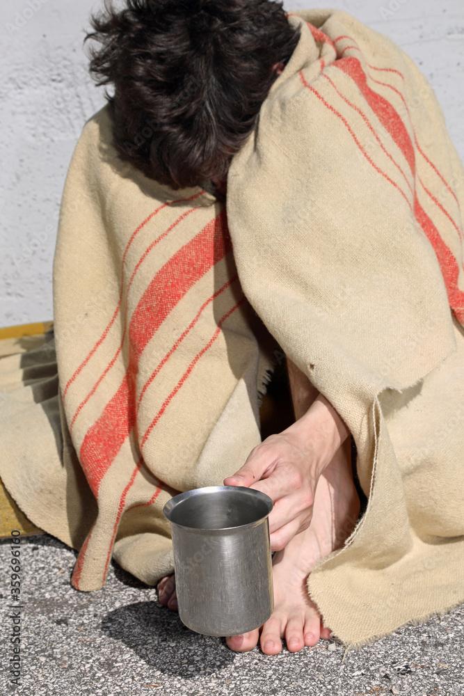 Fototapeta desperate young homeless man asks to dissolve passersby under a