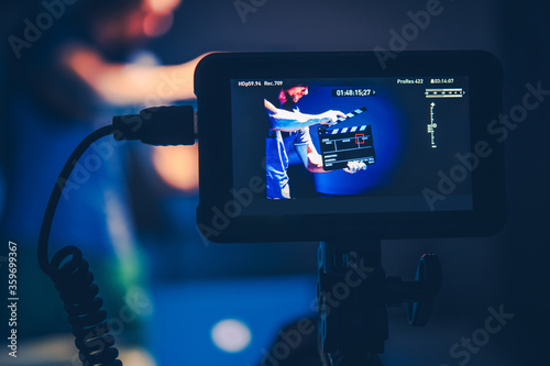 Fényképezés Camera Operator Taking Shots of Men with Clapperboard