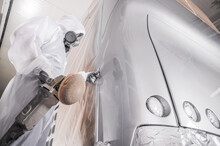 Professional Body Shop Worker Polishing Newly Painted Bus Body