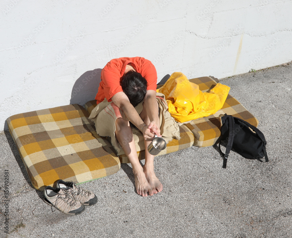 Fototapeta homeless man asks for charity for a long time on a street of the