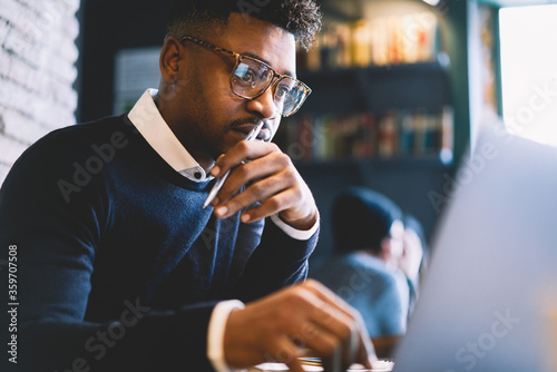Skilled afro american IT developer in glasses concentrated while coding app for Wallpaper Mural