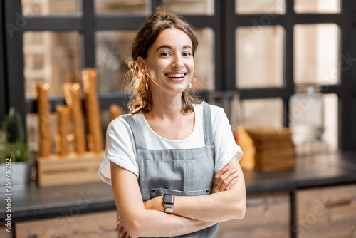 Fototapeta Portrait of a young and happy saleswoman at the counter in ice cream shop or cafe. Concept of a small business and retail obraz