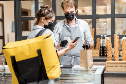 Female courier taking online order for delivery at the counter with salesperson in the small pastry shop or cafe. Concept of a take away food during pandemic - 359724544