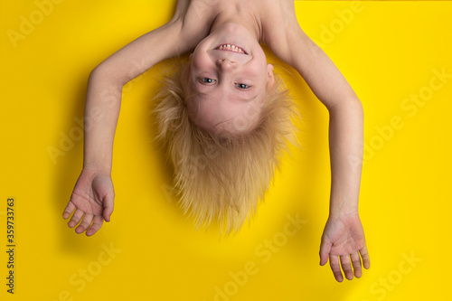 Fotomural Funny boy with blond hair hanging upside down on yellow background