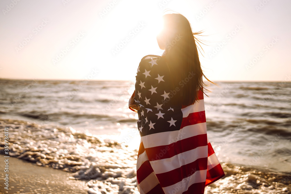 Fototapeta Girl with american flag on the beach at sunset. 4th of July. Independence Day. Patriotic holiday.