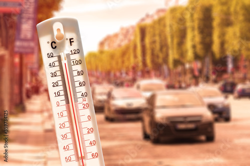 Thermometer in front of cars and traffic during heatwave Canvas