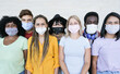Happy multiracial friends laughing and wearing protective face mask - Group of young peoples having fun together - Concept of lifestyle, health care and the new normality