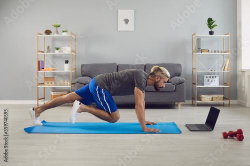 Fototapeta Fit sportsman doing mountain climber exercise online training at home obraz