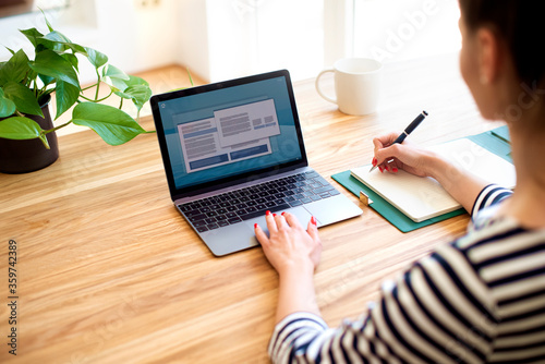 Fototapeta Back view of unrecognizable woman working on laptop in the office obraz