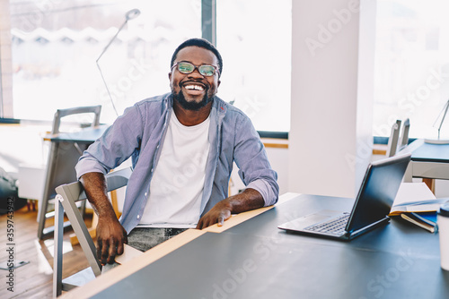 Obraz Happy casually dressed dark skinned male laughing sitting at desktop enjoying working process, cheerful african american hipster guy satisfied with online business spending time in coworking space. - fototapety do salonu