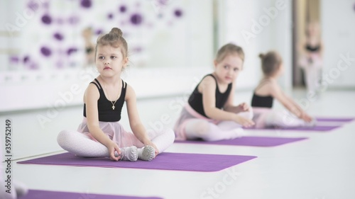 Foto Cute little ballerinas stretching together at dancing school