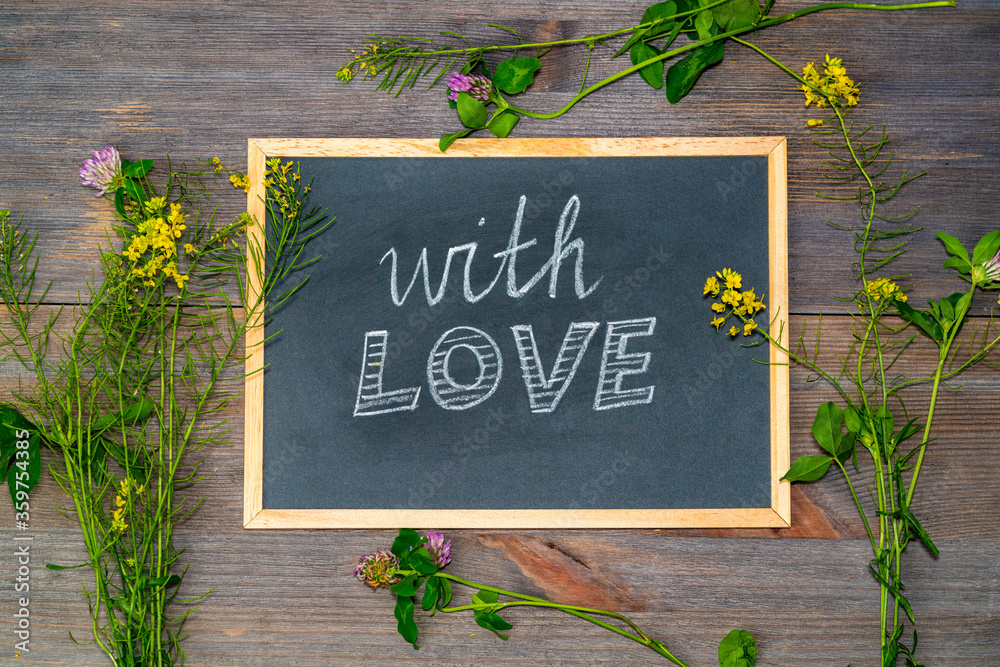 Fototapeta blackboard with the phrase with love written on it with flowers around her.