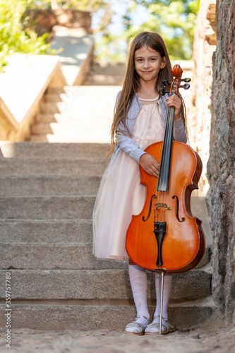 Fotografie, Tablou beautiful girl in a dress with a cello stands on the steps