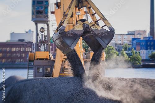 Obraz na plátně Bulk-handling crane unloading sand, road metal and gravel from cargo vessel ship