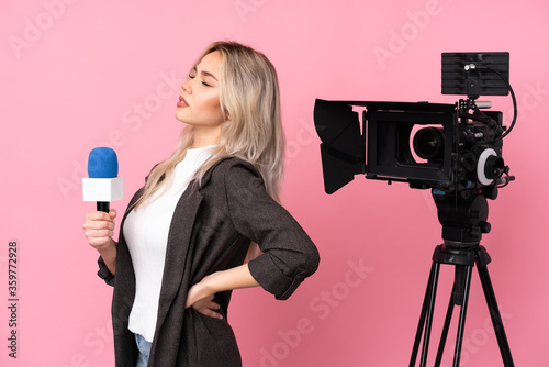 Fotomural Reporter woman holding a microphone and reporting news over isolated pink backgr