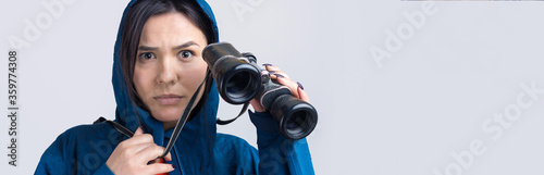 Fototapeta A tourist girl in a blue raincoat holds binoculars in her hands and looks into the distance, spies