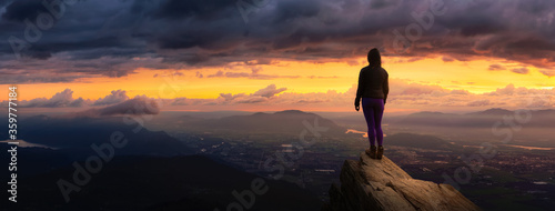 Fotomural Fantasy Adventure Composite with a Girl on top of a Rock Cliff with Beautiful Nature in Background during Sunset or Sunrise