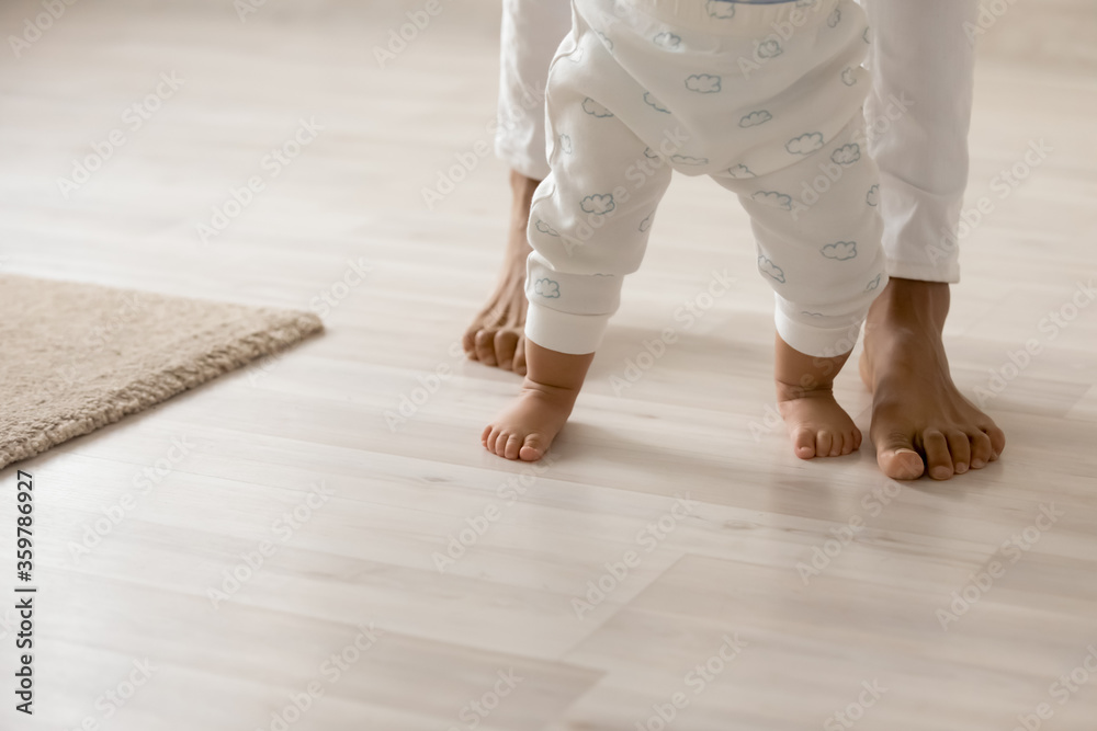 Fototapeta Close up barefoot African American woman with toddler child standing on warm wooden floor with underfloor heating, caring loving young mum teaching adorable little daughter to walk at home