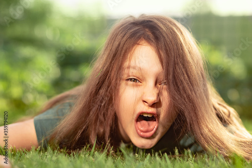 Crazy angry kid girl shouting with opened mouth and mad hair lying on the green grass on outdoor summer background Fototapet