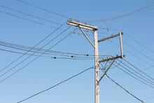 Utility Pole With Many Lines Against A Blue Sky