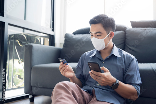 Fototapeta Asian man work from home ordering product online from ecommerce store, using mobile phone credit card payment transaction, wearing facemask protection from coronavirus covid-19 in quarantine isolation obraz