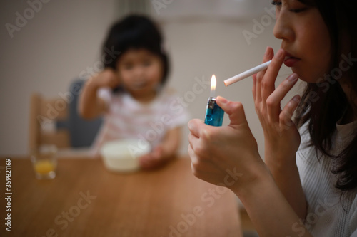Photo 子供の近くで喫煙する母親
