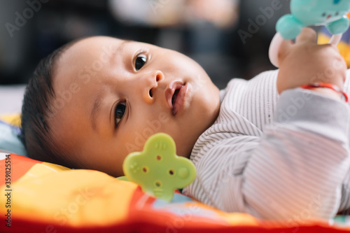 Baby boy playing with a toy with a innocent expression Fototapet